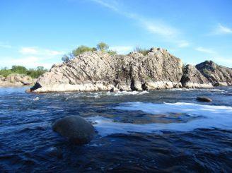 Каменная скала, повернувшая поток воды.